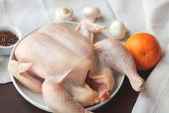 Pollo crudo con i mashrooms ed arancia sulla tavola di legno scura Fotografia Stock