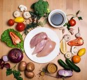 Pollo crudo del prendedero Carne fresca del pollo en la placa blanca en de madera Fotografía de archivo libre de regalías