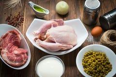 Pollo crudo entero con los ingredientes en fondo de madera imagen de archivo libre de regalías