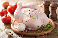 Pollo crudo entero con pimienta y tomillo color de rosa Fotografía de archivo libre de regalías