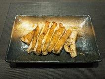 Pollo de Teriyaki en plato negro Foto de archivo