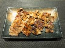 Pollo de Teriyaki y cerdo asado a la parrilla en plato negro Fotografía de archivo libre de regalías