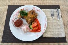 Pollo de una barbacoa con un adorno de verduras frescas Imagen de archivo