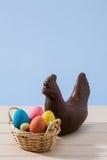 Pollo del chocolate de Pascua y huevos coloreados sobre una tabla blanca Imagen de archivo