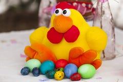 Pollo del juguete de Pascua con los huevos de Pascua coloridos Foto de archivo libre de regalías