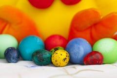 Pollo del juguete de Pascua con los huevos de Pascua coloridos Imagen de archivo libre de regalías