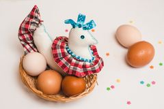 Pollo del juguete y huevos coloreados del pollo en una cesta marrón de mimbre y decoraciones de los pasteles foto de archivo libre de regalías