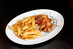 Pollo delicioso y picante con la decoración de los brotes de Fried Potatoes y de la cebolla Imagenes de archivo