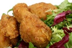 Pollo di sorgente fritto nel grasso bollente nella pastella dorata del limone con insalata Immagine Stock