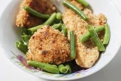 Pollo en migajas de pan con las habas verdes y el bróculi en una placa blanca Foto de archivo libre de regalías