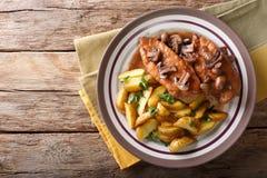 Pollo en salsa de la marsala con las setas y las patatas fritas cerca Imagen de archivo