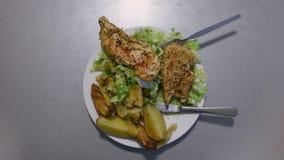 Pollo, ensalada y patatas en una placa El frente de la cámara gira, rotación del lazo, metrajes