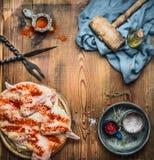 Pollo entero aplanado hacia fuera con el martillo de la carne, las especias y las herramientas de la cocina en el fondo rústico d foto de archivo