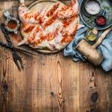 Pollo entero aplanado hacia fuera con las herramientas del condimento y de la cocina en el fondo rústico de madera, cocinando la  fotografía de archivo