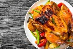 Pollo entero asado, patatas, zanahorias de bebé, berenjenas, verdes imagenes de archivo