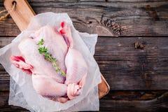 Pollo entero crudo orgánico en fondo de madera fotos de archivo