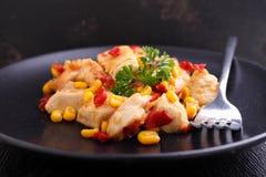 Pollo frito con maíz y pimientas rojas dulces Imagenes de archivo