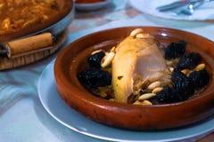 pollo Lento-cocinado con las pasas, almendras, cebollas y asperjado con el s?samo, tagine marroqu? fotos de archivo