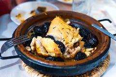 pollo Lento-cocinado con las pasas, almendras, cebollas y asperjado con el s?samo, tagine marroqu? imagenes de archivo