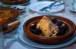 pollo Lento-cocinado con las pasas, almendras, cebollas y asperjado con el s?samo, tagine marroqu? fotografía de archivo libre de regalías