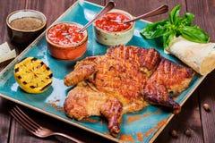 Pollo o pavo asado con las especias, el limón, la salsa de tomate, la albahaca y el pan Pita en la placa en fondo de madera oscur Fotografía de archivo