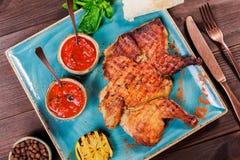 Pollo o pavo asado con las especias, el limón, la salsa de tomate, la albahaca y el pan Pita en la placa en fondo de madera oscur Imagenes de archivo