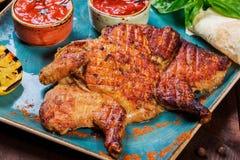Pollo o pavo asado con las especias, el limón, la salsa de tomate, la albahaca y el pan Pita en la placa en fondo de madera oscur Imagen de archivo libre de regalías