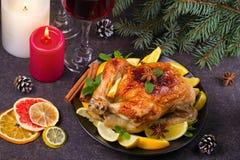 Pollo o pavo con los limones, las naranjas, las cales y las especias en fondo de la Navidad y del Año Nuevo Imagen de archivo