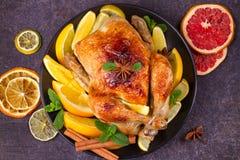 Pollo o pavo con los limones, las naranjas, las cales y las especias en fondo de la Navidad y del Año Nuevo Fotografía de archivo libre de regalías