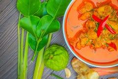 Pollo rojo del curry, comida picante tailandesa e ingredientes frescos de la hierba en la visión superior/aún la vida de madera,  Fotos de archivo libres de regalías
