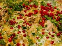 Pollo in salsa del latte con coriandolo, prezzemolo, le spezie e il pomegra immagine stock