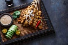 Pollo Satay o Sate Ayam - comida famosa del malasio Es un plato de la carne sazonada, ensartada y asada a la parrilla, servida co imagen de archivo