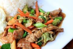 Pollo tailandés delicioso del plato con las verduras sofritas en el plato blanco con arroz y el huevo frito en la tabla de madera Fotografía de archivo libre de regalías