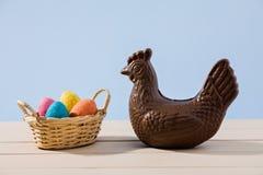 Pollo y huevos del chocolate de Pascua sobre una tabla Foto de archivo