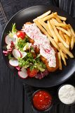 Pollock in breadcrumbs garnished with French fries and fresh salad closeup. Vertical top view stock photo