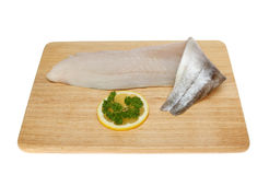 Pollock fillet. Pollock fish fillet on a wooden board isolated against white stock photo