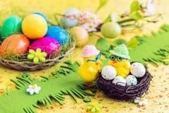 Pollos con los huevos de Pascua en la jerarquía Imágenes de archivo libres de regalías