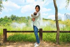Polluelo infantil asiático en el mother& x27; pecho de s imagen de archivo