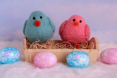 Polluelos del bebé con los huevos coloridos en frente Imagen de archivo libre de regalías