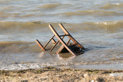 Polluted beach with a chair in it. Stock Photos