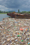 Polluted river bank full of garbage royalty free stock photos