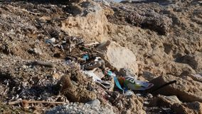 Polluted rocky beach filled with plastic and garbage. Environmental problems concept. Slow motion.  stock footage