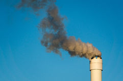 Polluted smoke against a clear blue sky from the tall chimney Stock Photography