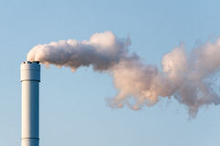 Polluted smoke against a clear blue sky from the tall chimney Royalty Free Stock Photos