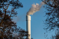 Polluted smoke against a clear blue sky from the tall chimney Royalty Free Stock Photography