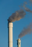 Polluted smoke against a clear blue sky from the tall chimney Royalty Free Stock Image