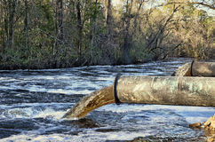 Pollution. Polluted water rushing into a pristine river Stock Image
