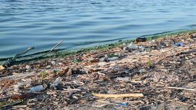 Polluted water and trash on a beach. Water pollution with dirty water and trash and plastic wastes on a beach stock video