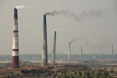 Polluting air brick factories pipes at Dhaka, Bangladesh. Royalty Free Stock Photo