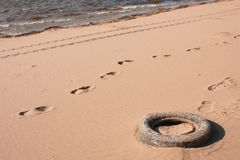 Polluting car tire in the sand on the beach near the water stock image